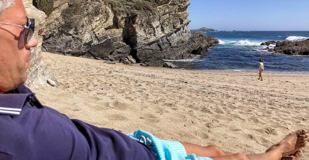Man relaxing at Praia dos Buzuinhos beach in Portugal