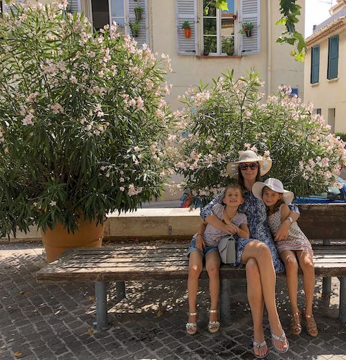 Mother and 2 daughters taking a break at a bench near the church of Cassis South of France