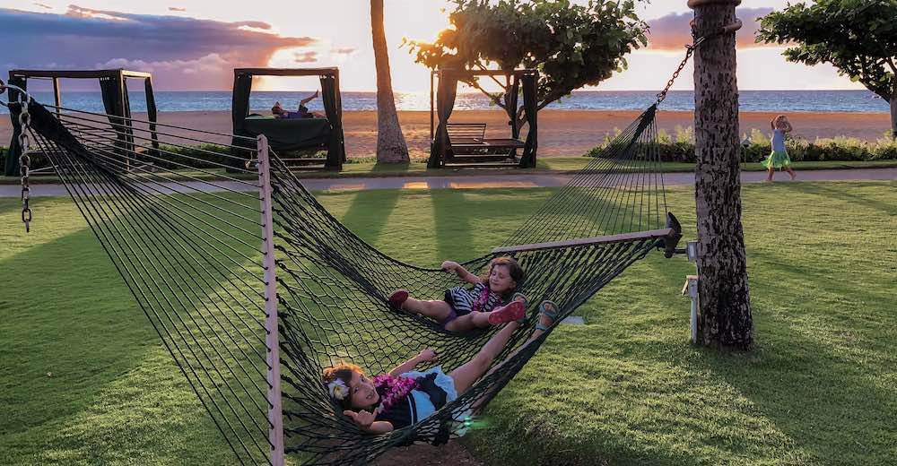 Two little girls in hamocks at Kaanapali beach, a very family-friendly place to stay in Maui Hawaii