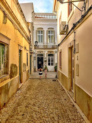 Two little girls exploring the cobbled streets of Loule near Faro Portugal