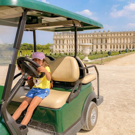 Little girl exploring the Gardens of Versailles by electric cart