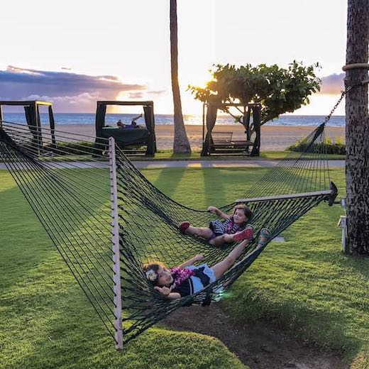 Two girls in a hammock at the best Hawaii island for family