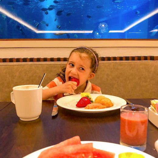 Little girl having breakfast at the Alohilani Resort Waikiki beach