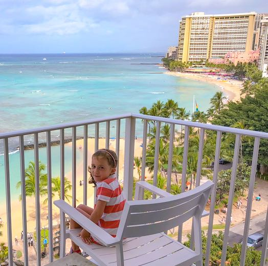 Oahu is the best Hawaii island for families that prefer city life like this girl on her Waikiki balcony