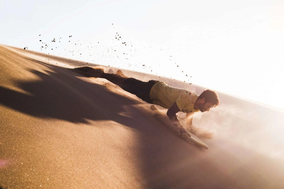 How to develop charisma and self-confidence, cover photo representing a man surfing on the sand.