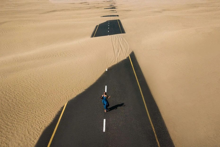Girl standing over a road covered by sand