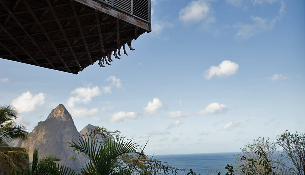 Friends swing their legs off the Cantilever at Cosmos St Lucia while enjoying the view of the Pitons mountains