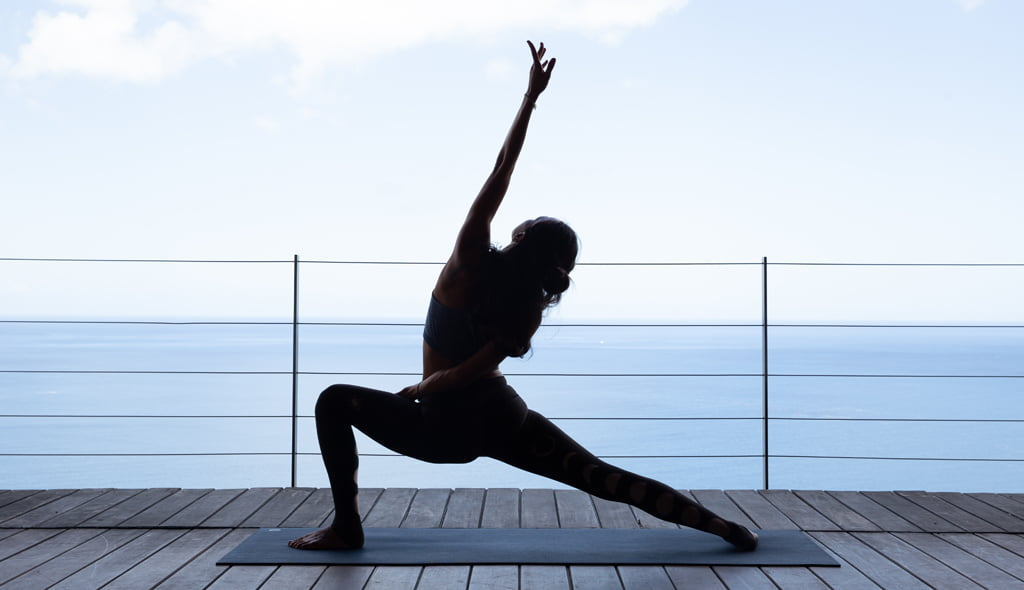 A woman practising yoga at Cosmos St Lucia luxury villa while overlooking the sea