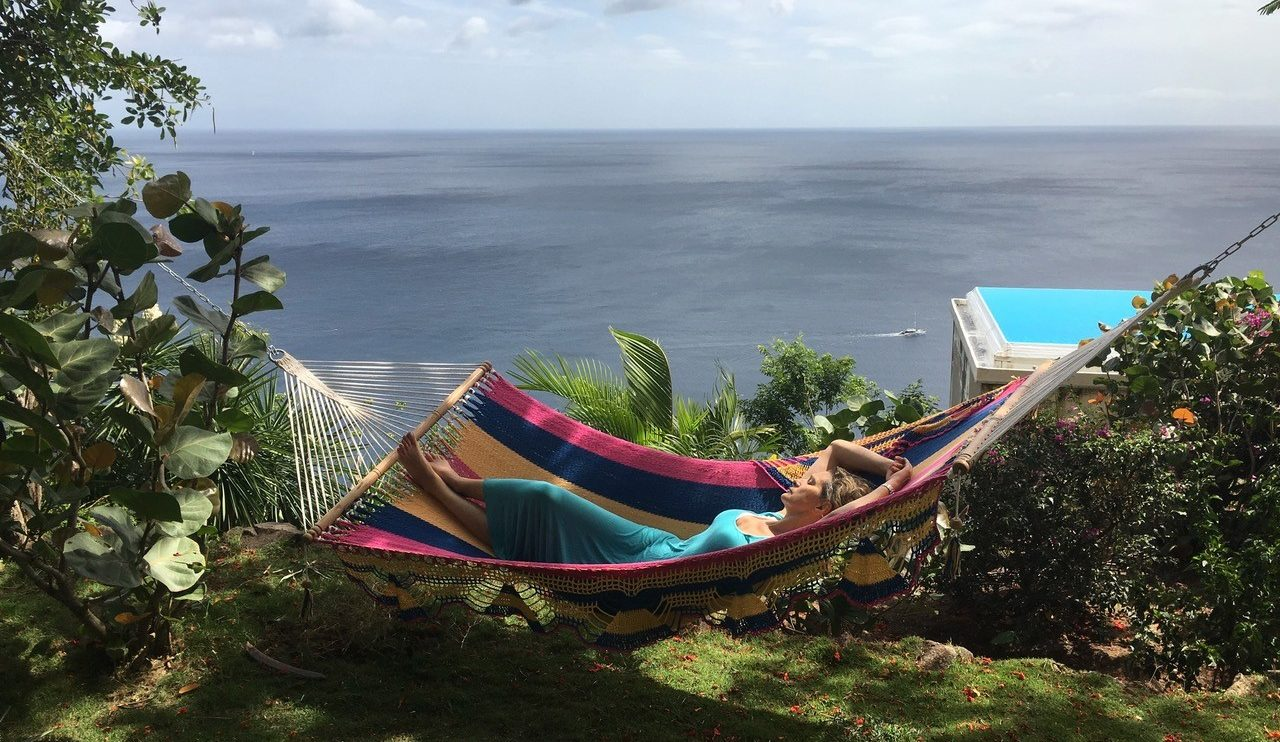 A woman relaxes in a colourful hammock at Cosmos St Lucia, with the infinity pool and Carribean Sea in the background