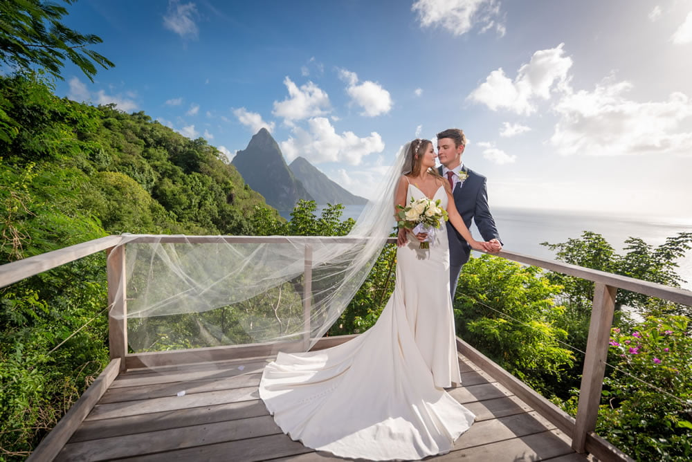 A newly married couple embrace on the The Lodge deck with the Pitons in the background