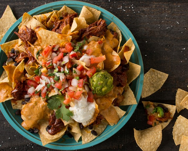 A plate of Costa Vida nachos covered in pico de gallo, queso and guacamole.