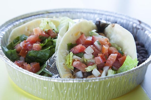 A pair of steak tacos topped with lettuce and pico de gallo sit in a serving tin with a side of black beans.