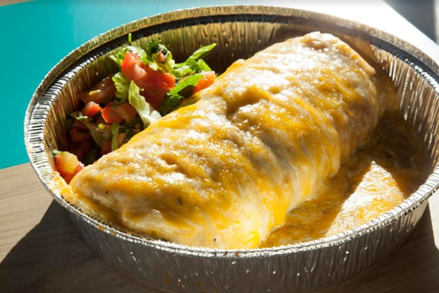 A burrito smothered in sauce and melted cheese sits in a tin container, with lettuce and pico de gallo on the side.