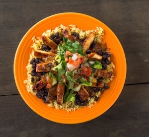 A grilled chicken burrito bowl, with rice and black beans on the bottom and sauce, lettuce and pico de gallo on top, in an orange bowl on a wooden table.