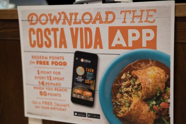 "An in-store advertisement for the Costa Vida app, with a phone displaying the app next to a plate with a smothered burrito. Text at the top reads ""Download the Costa Vida App."""