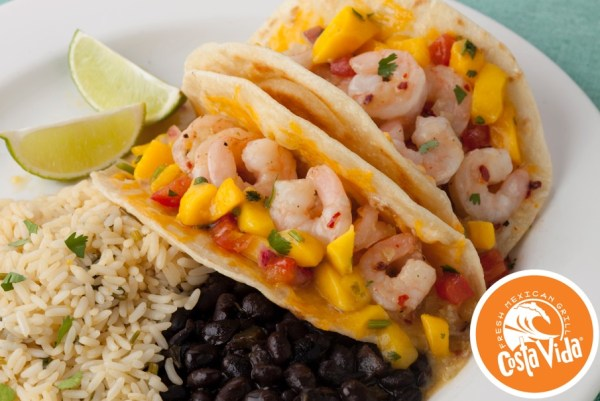 An image of shrimp tacos with mango salsa, plated next to rice, black beans and two lime wedges. The Costa Vida logo is in the lower-right corner.