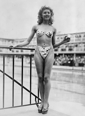 Micheline Bernardini modeling Réard's bikini at the Piscine Molitor. It was small enough to fit into a 5 by 5 centimetres (2.0 by 2.0 in) box like the one she is holding. July 5, 1946.