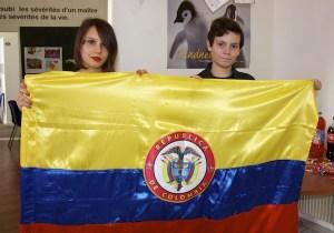 Felicia y Luis Eduardo sujetan la bandera de Colombia