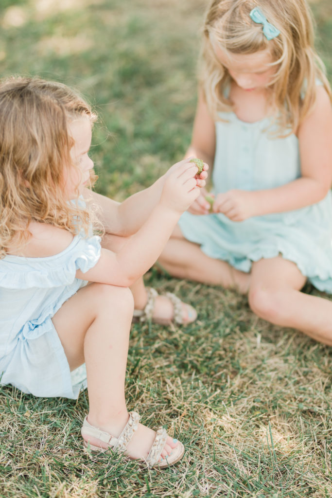 Girls playing in the grass at Playful Beach Family Session in Southern Maryland by Costola Photography