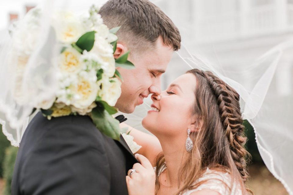 bride and groom kissing under veil for black and white winter wedding at the kyle house by costola photography