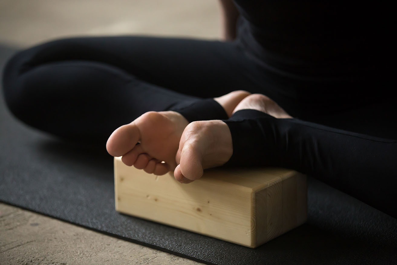Yogi sporty woman practicing yoga concept, sitting in Butterfly exercise, advanced baddha konasana pose, using wooden block, working out, wearing sportswear pants, white loft background, legs close up