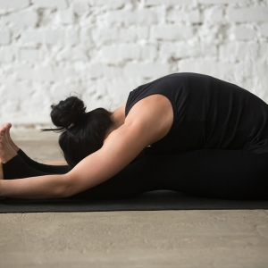 Young yogi woman practicing yoga concept, sitting in paschimottanasana exercise, using wooden block, seated forward bend pose, wearing black sportswear, working out, full length, white loft background