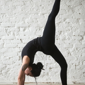 Young yogi woman practicing yoga concept, doing One legged Wheel exercise, Bridge pose, working out wearing sportswear black tank top and pants, full length, white loft background. Vertical photo