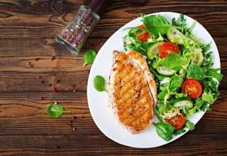 Peito de frango grelhado e salada de legumes fresca - tomates, pepinos e folhas de alface vista de cima.