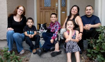 Integrity Housing Landlord Pam Rosen poses with the family now safely housed in her rental home. Thank you, landlords!