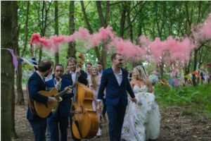 Wandering band and pink smoke in the woods post ceremony towards the tipi wedding