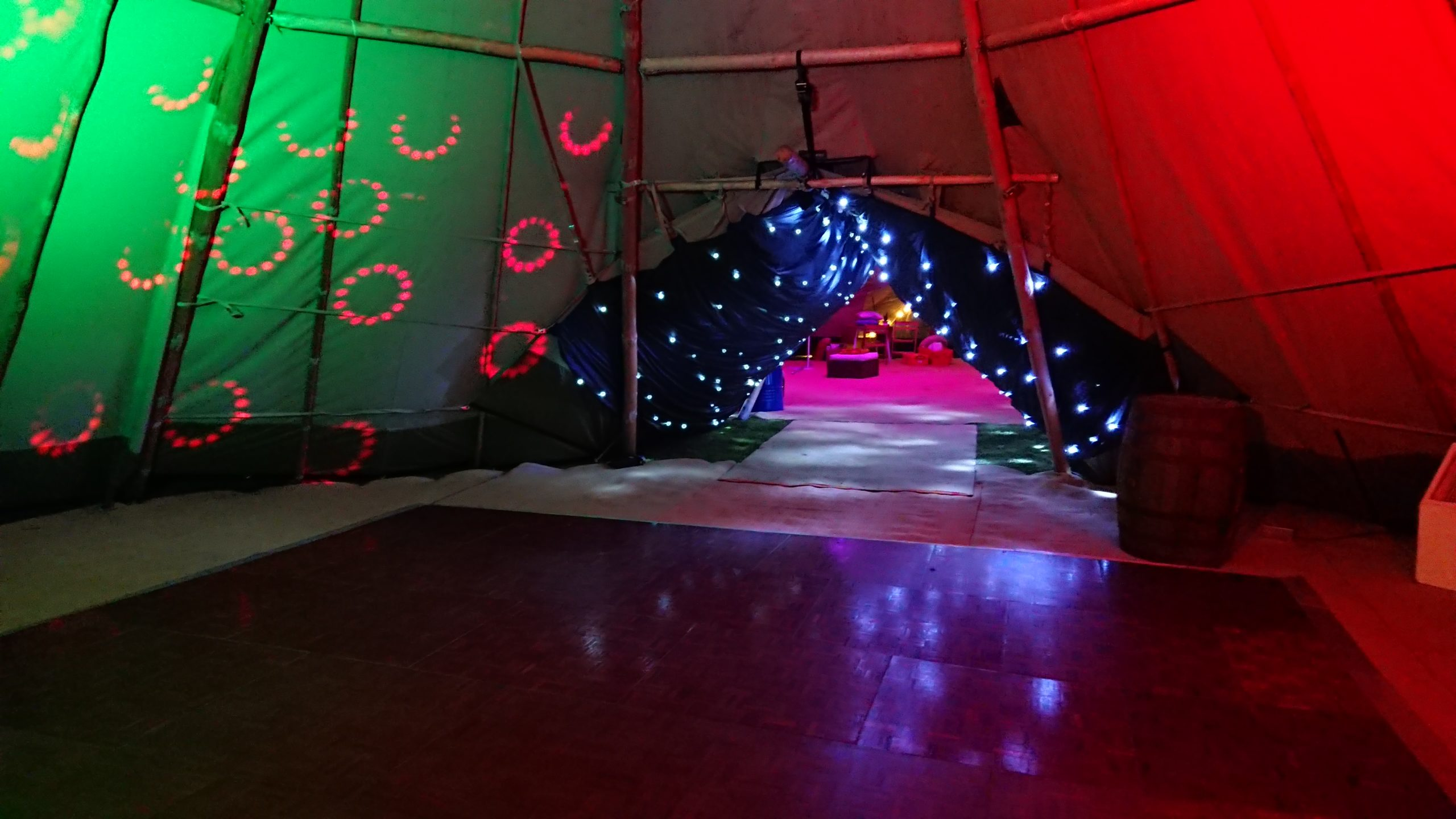 Unique tipi set up with dance floor area looking through starry tunnel to the bar and sofa area