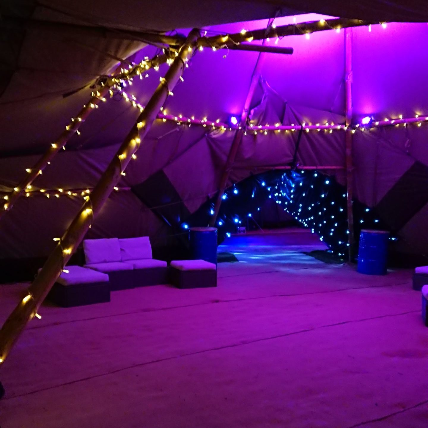 Unique tipi set up with bar and sofa area and starry tunnel to the next tipi