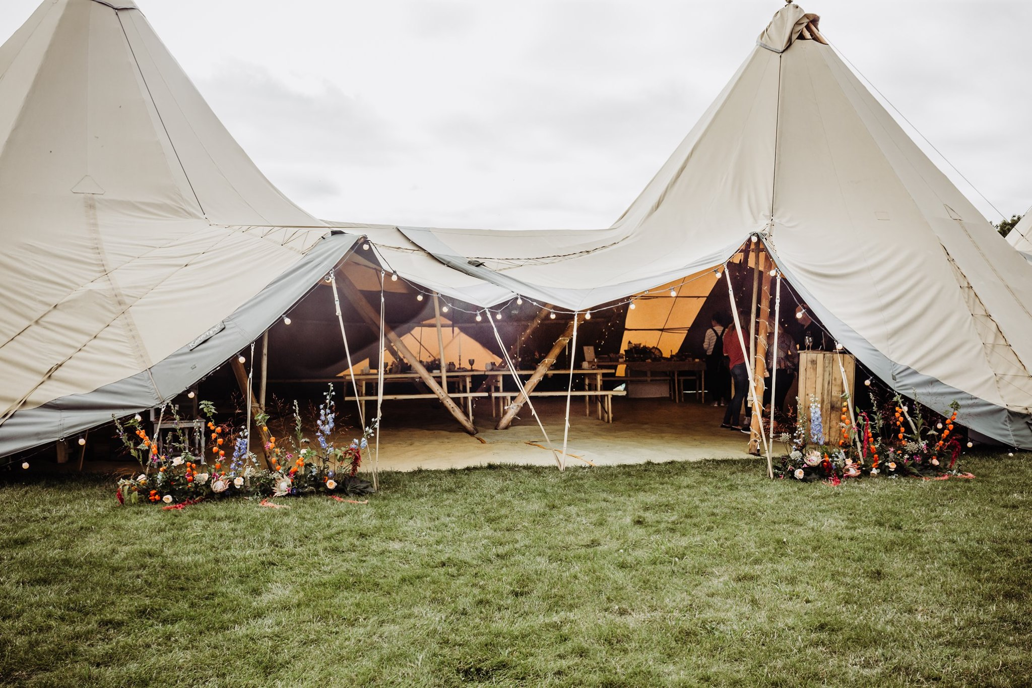 Photo of the entrance to 3 tipis with colourful, free-standing, wild flower displays on either side of entrance