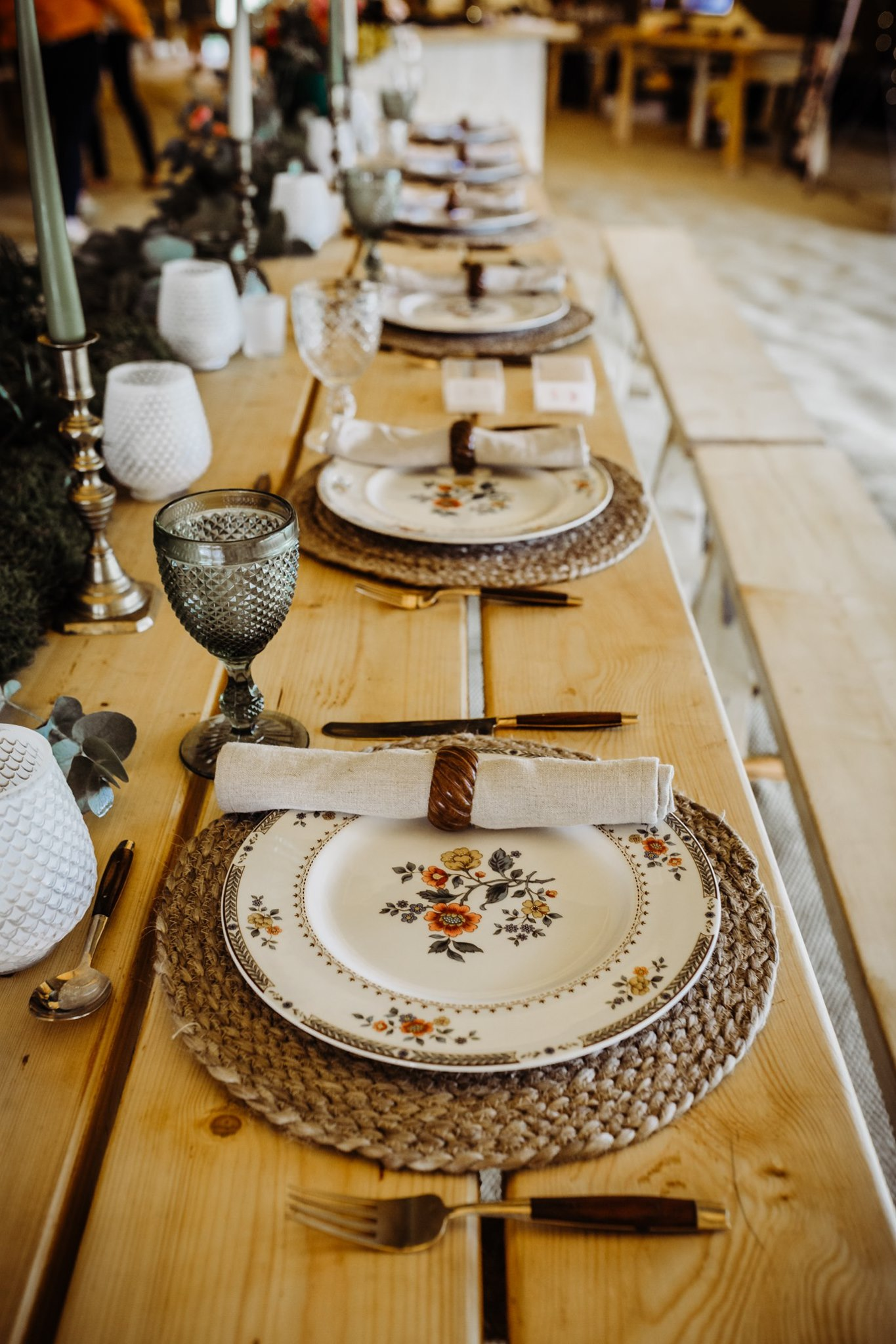 Close up photo of Sally's Secrets wedding prop hire including rustic tableware, linen napkins, wooden napkin rings, textured glassware and tall candlesticks.