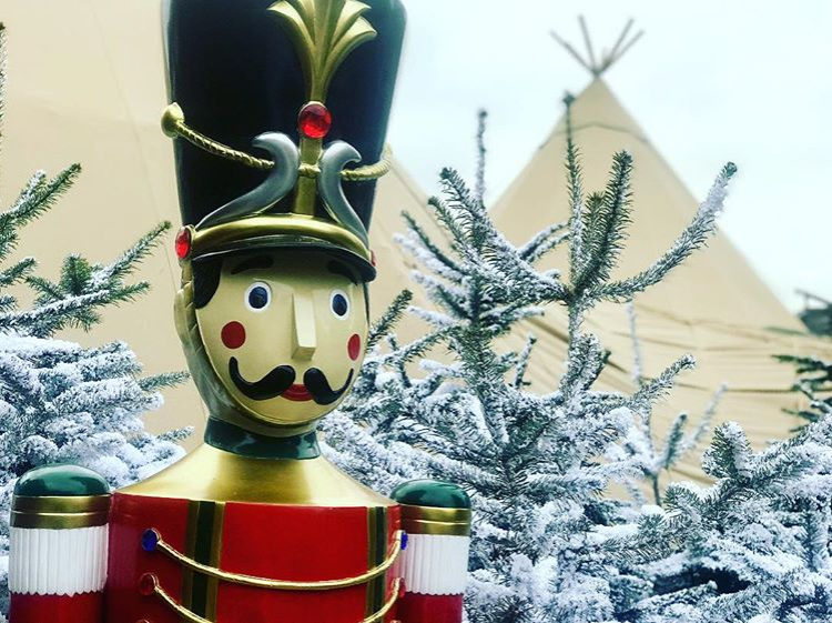 Image of wooden life-size nutcracker doll next to two Giant Hat Tipis at Gloucester Christmas Markets.