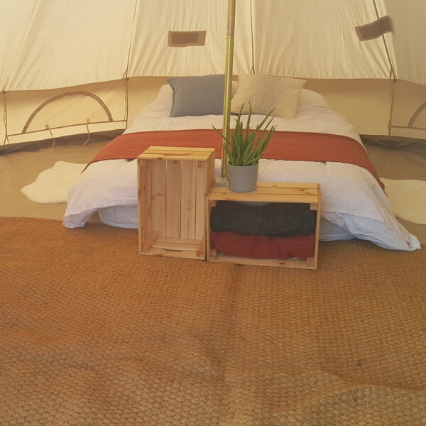 Photo of Cotswold Tipis Honeymoon Bell Tent with air mattress, bedding, cushions, chest with blankets, fairy lights, wicker seat and decorative plant