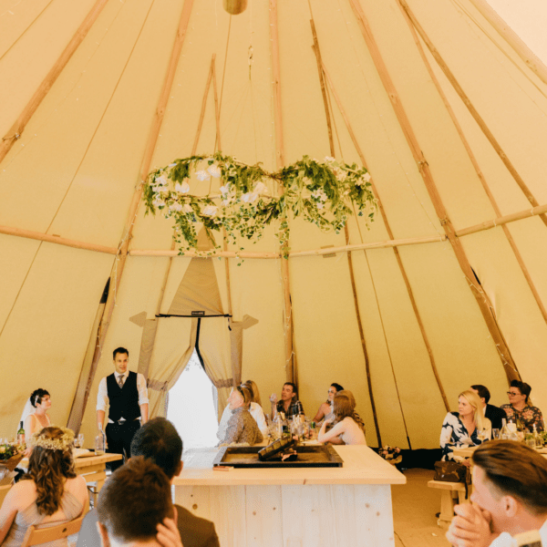 Image of the inside of one tipi with tables places around a central fire pit at a tipi wedding.