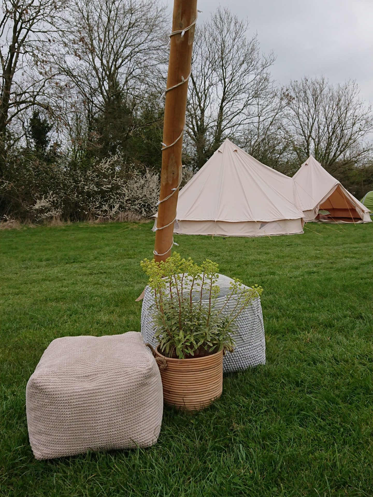 2 Bell tents beside giant naked tipi with fairy lights and soft furnishings, styled by Wedding Creations UK