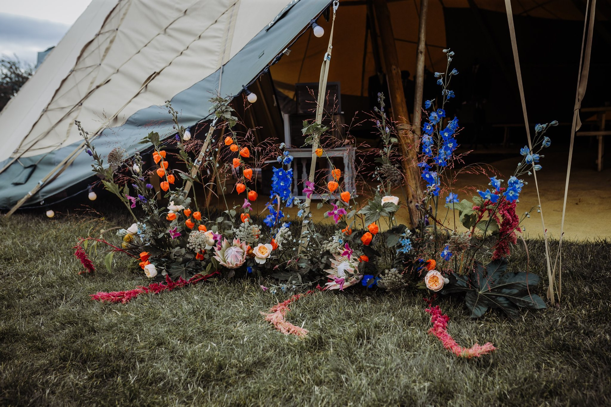 Free standing wild flower display at the entrance to three Giant Tipis ideal for magical outdoor weddings