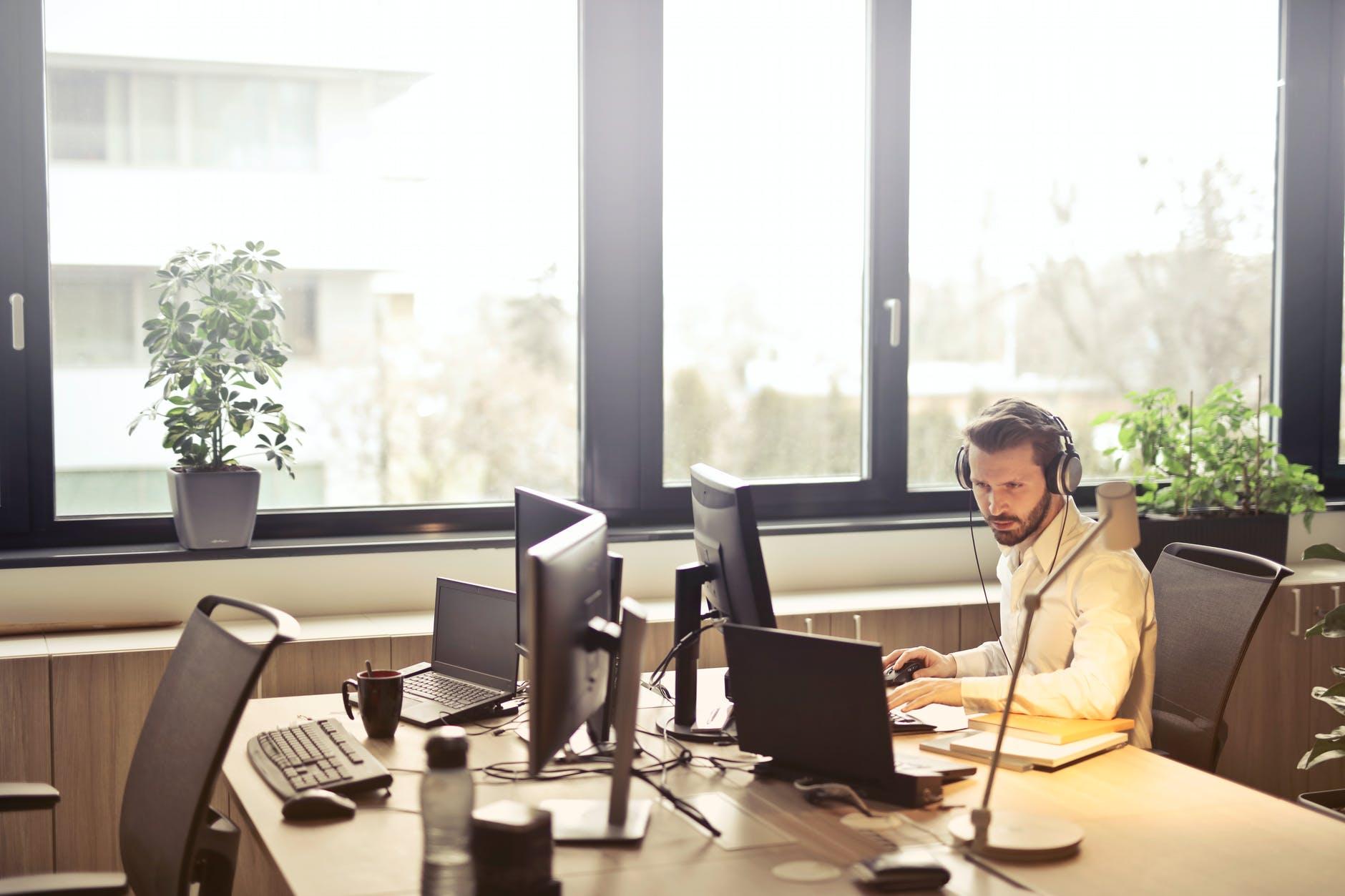 man with headphones facing computer monitor