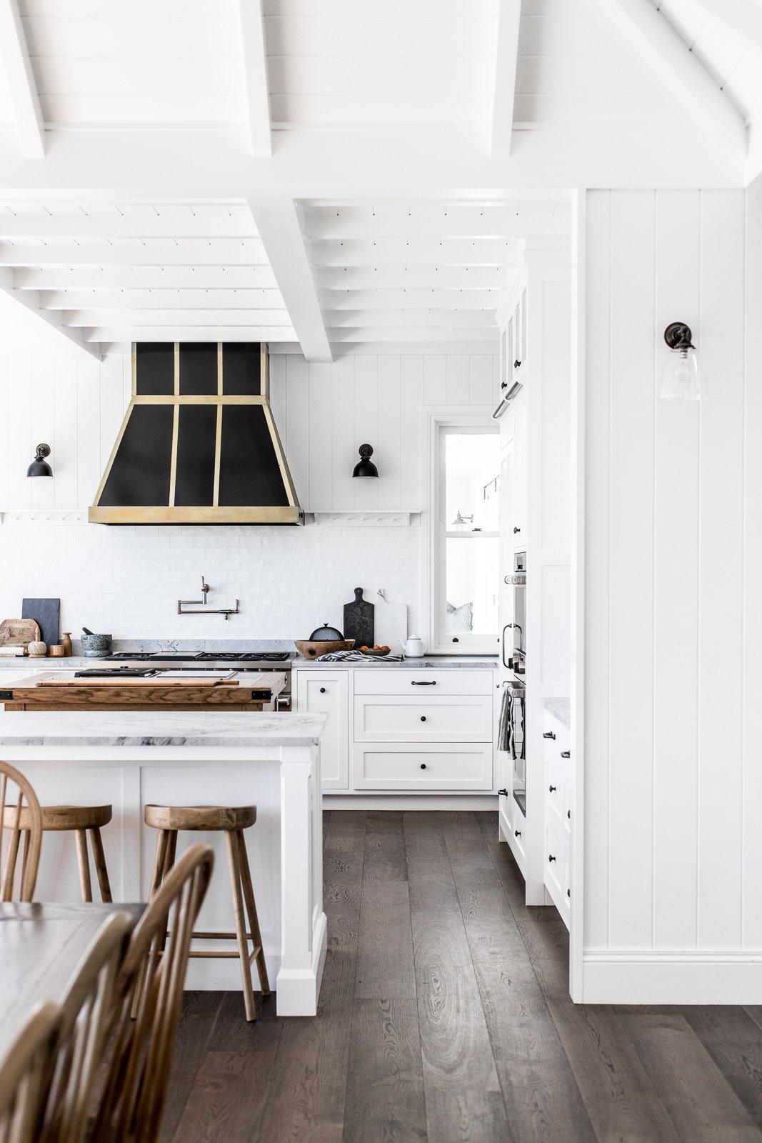 white shaker kitchen with oak floors and metal range