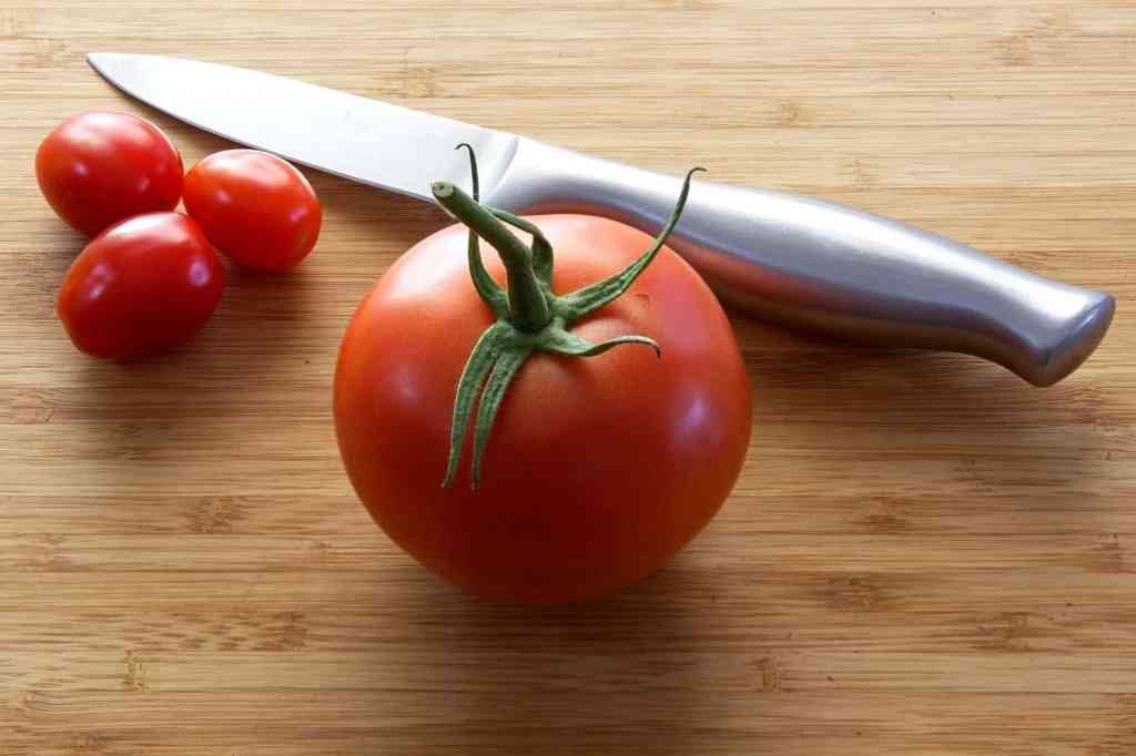 3 cherry tomatoes, a large tomato, and a knife