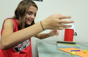 Eighth grader Haley Loftis rolls a pair of dice during a probability activity in Mrs. Lydia Henry's Math 8 class. During the activity, students created ratios to determine the probability of an event. (This photo earned an Honorable Mention for photographer Lauren Powell.)
