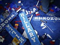 """A worker walks past a """"Hillary"""" sign on the floor after the Democratic National Convention (DNC) in Philadelphia, Pennsylvania, U.S., on Thursday, July 28, 2016. Division among Democrats has been overcome through speeches from two presidents, another first lady and a vice-president, who raised the stakes for their candidate by warning that her opponent posed an unprecedented threat to American diplomacy. Photographer: Andrew Harrer/Bloomberg via Getty Images"""