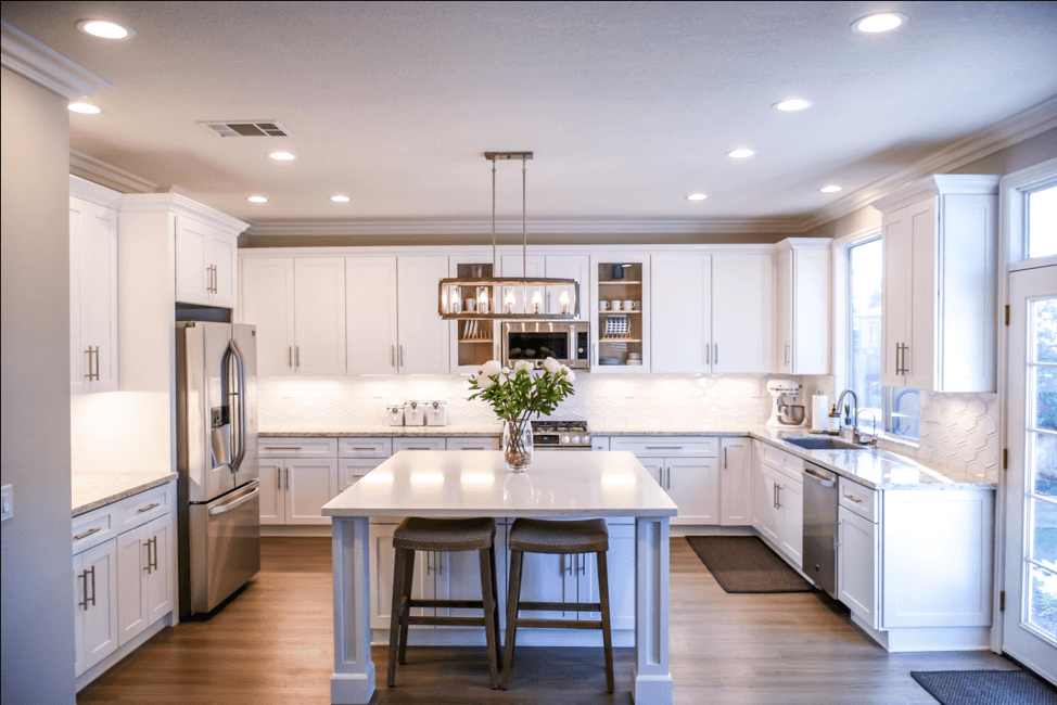 A wide shot of a white kitchen with clean quartz countertops