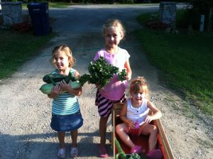 Girls holding veggies from a community garden we go to up in northern Michigan on Old Mission Peninsula