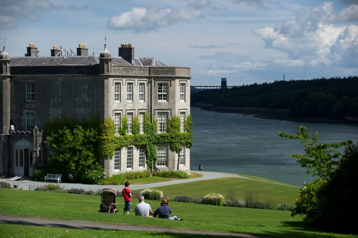 Visitors sitting on a lawn next to the house at Plas Newydd Country House and Gardens, Anglesey, Wales.