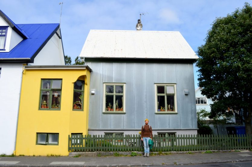 Reykjavik Gay Travel Daan in front of a grey and yellow house | Gay Couple Travel City Weekend Reykjavik Iceland © Coupleofmen.com
