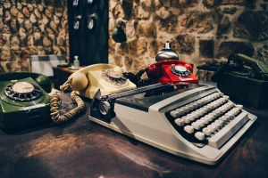 """A green, red, and white telephone and a type writer at Escape Room """"Bunker"""" from Fox in a Box © CoupleofMen.com"""