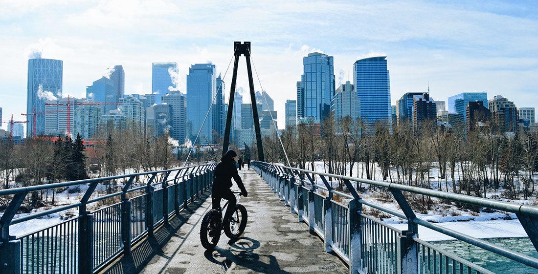 Karl on his Fat Bike in front the Skyline of Calgary | Fat Tire Biking Calgary Nomad Gear Rentals © CoupleofMen.com